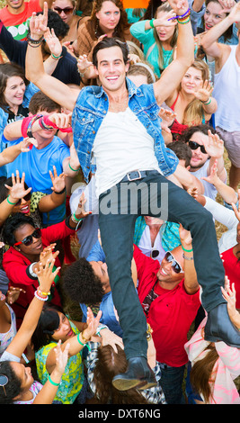 Portrait of man crowd surfing at music festival - Stock Photo