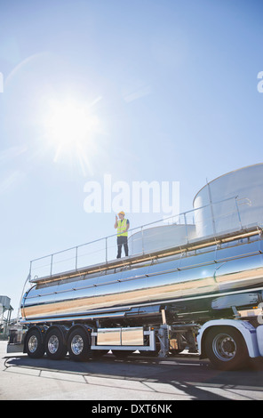 Worker standing on platform above stainless steel milk tanker - Stock Photo