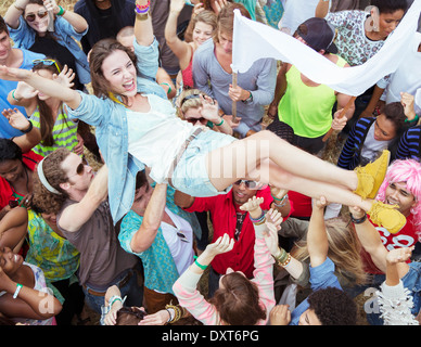 Woman crowd surfing at music festival - Stock Photo
