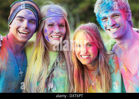 Close up portrait of friends covered in chalk dye at music festival - Stock Photo