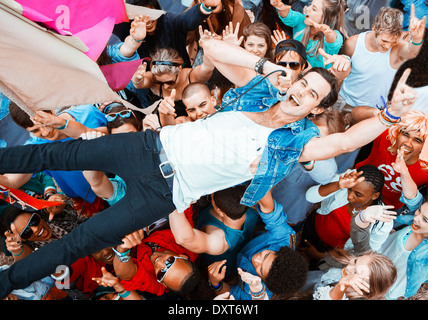 Performer singing and crowd surfing at music festival - Stock Photo