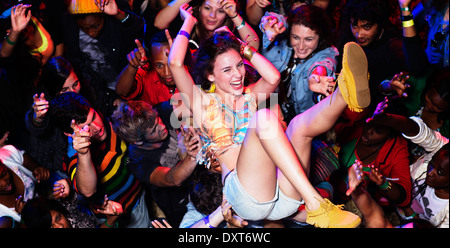 Enthusiastic woman crowd surfing at music festival - Stock Photo