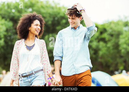 Couple holding hands outside tents at music festival - Stock Photo