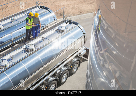 Workers on platform above stainless steel milk tanker - Stock Photo