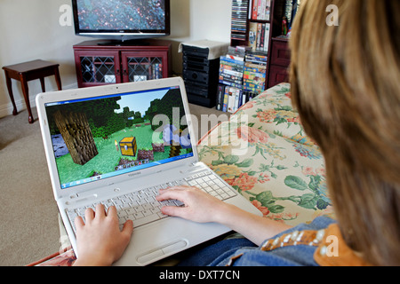 a teenage boy playing Minecraft on a laptop computer whilst watching television - Stock Photo