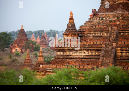 Tourists on a Buddhist temple waiting for sunset in Bagan, Myanmar - Stock Photo