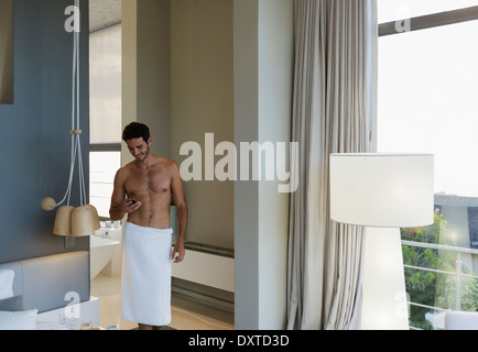 Man in towel texting with cell phone in bedroom - Stock Photo