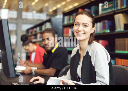 Beautiful young caucasian student sitting at table with computer looking at camera smiling. Young university students. - Stock Photo