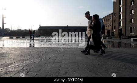 Students walking past fountain outside UAL Central St Martins Art College in Granary Square, Kings Cross London - Stock Photo