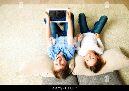 Children using tablet computer at home, having fun, Munich, Bavaria, Germany - Stock Photo
