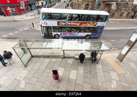 Looking down on a UK city street and bus stop with people waiting and a double decker bus passing. Sheffield, Yorkshire, - Stock Photo
