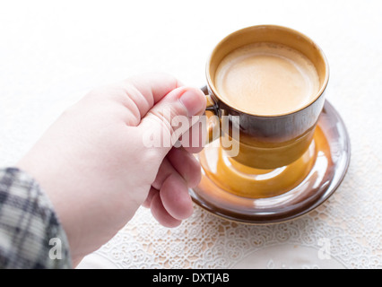 Cup of delicious coffee on a white tablecloth. - Stock Photo