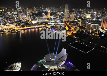 ArtScience museum iluminated in front of Singapore downtown. View from Marina Bay Hotel - Stock Photo