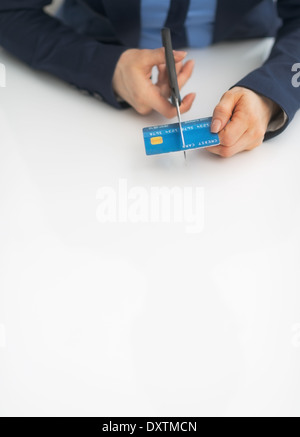 Closeup on business woman cutting credit card with scissors - Stock Photo