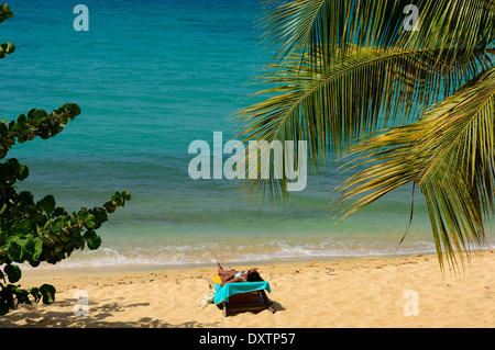 Young woman sunbathing on Magazine beach. Grenada - Stock Photo