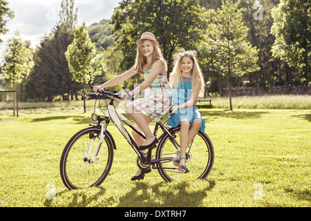 two teenage girls cycling in a summerly park - Stock Photo