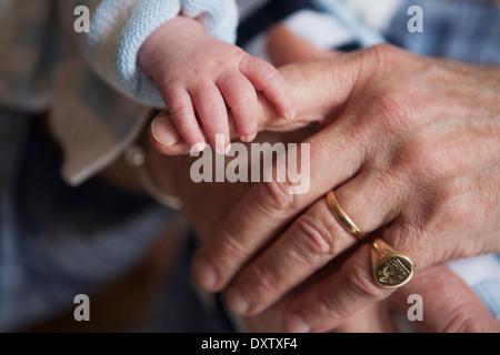 Newborn baby holds grandfather's forefinger; Toronto, Ontario, Canada - Stock Photo