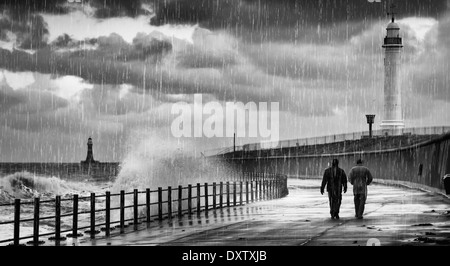 Two people walking along the shore at the water's edge in the rain and waves a lighthouse in the background; Sunderland, - Stock Photo