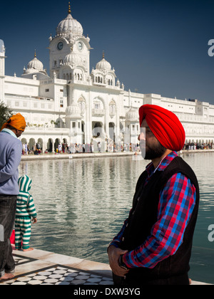 India, Punjab, Amritsar, Sri Harmandir or Darbar Sahib, Sikh man wearing red turban beside the Golden Temple Gurdwara - Stock Photo