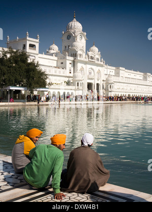 India, Punjab, Amritsar, Sri Harmandir or Darbar Sahib, Golden Temple Sikhs sat beside Sarovar holy tank - Stock Photo