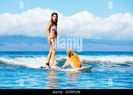 Attractive Young Woman Surfing with her Dog. Riding Wave Together in Ocean. Surfing Dog. - Stock Photo