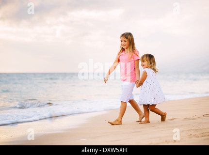 Adorable Young Sisters, Two Little Girls Walking together on the Beach at Sunet, Family Lifestyle. - Stock Photo