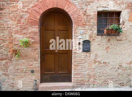 Wooden rounded door in Tuscany medieval town Certaldo Alto, Italy - Stock Photo