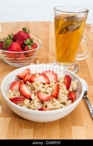 Bowl of millet breakfast pudding with strawberries and tea - Stock Photo