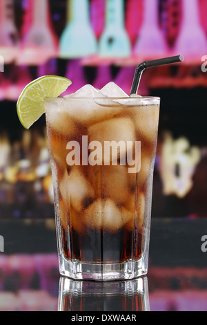 Cold cola drink in glass with ice cubes in a bar or a party - Stock Photo