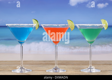 Colorful Cocktails in Martini glasses on the beach while on vacation - Stock Photo