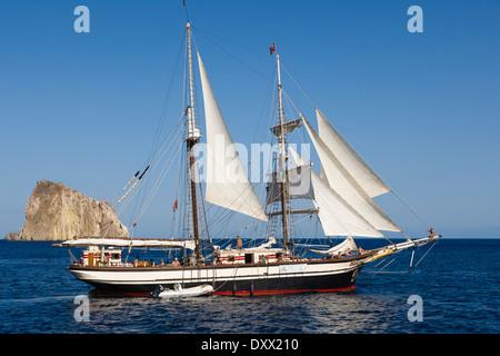 Yacht sailing off Isola Dattilo, volcanic island, Tyrrhenian Sea, Aeolian Islands, Sicily, Italy - Stock Photo