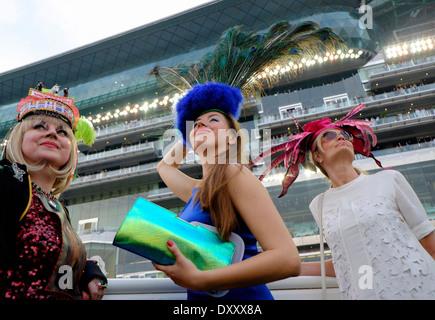Three fashionable ladies at the Dubai World Cup horse racing championship at Meydan racecourse in Dubai United Arab - Stock Photo