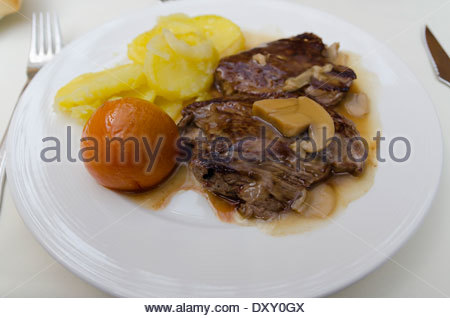 beef tenderloin in mushrooms sauce with potatoes and tomato - Stock Photo