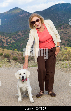 an pausing for a photograph with a six month old beige colored Golden Retriever dog on Tenderfoot Mountain, Salida, - Stock Photo