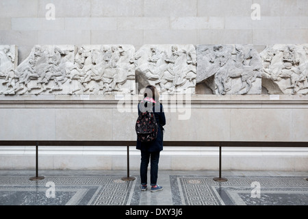 A tourist looks at a section of a frieze from the Elgin Marbles, British Museum, London. - Stock Photo