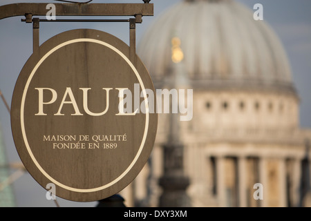 Paul Boulangerie Patisserie Bakery sign on Fleet Street with dome of St Paul's Cathedral in background London England - Stock Photo