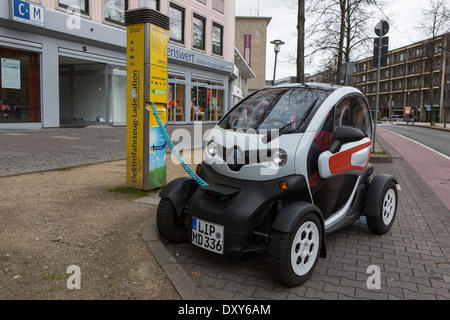An electric car having its battery re-charged - Stock Photo