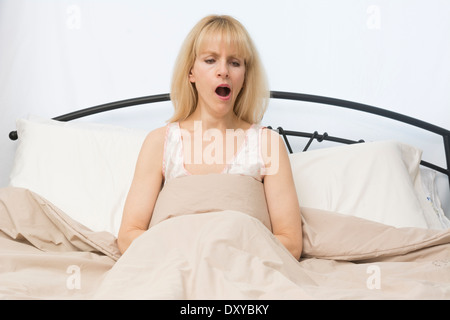 A middle age woman yawns as she wake up in morning - Stock Photo