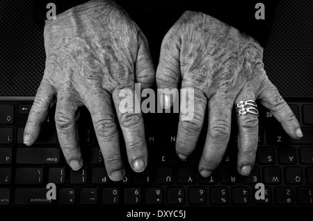 Closeup of old woman's hands with arthritis on computer keyboard in black and white - Stock Photo