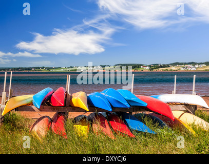 Colorful kayaks stored on Atlantic shore in North Rustico, Prince Edward Island, Canada - Stock Photo