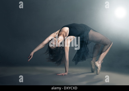 Modern style dancer posing on a studio grey background in fog - Stock Photo