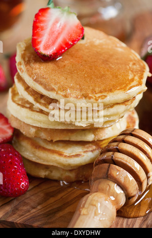 Homemade pancakes with ripe strawberry and honey. Selective focus. Close-up. - Stock Photo