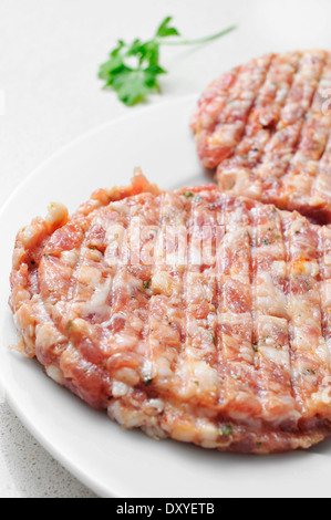 closeup of some raw spiced hamburgers in a plate - Stock Photo
