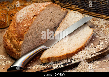 A freshly baked loaf of bread on a breadboard in farmhouse kitchen - Stock Photo