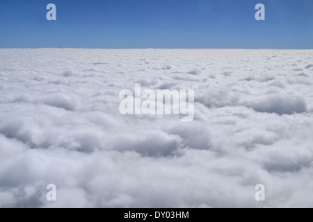 Puffy white cumulus from aircraft with blue sky - Stock Photo