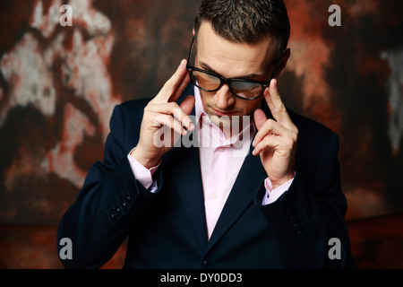 Cool fashion man in glasses standing over industrial background - Stock Photo