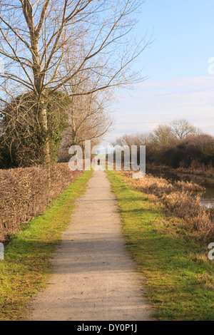 People walking in the distance along the Nottingham and Grantham Canal, Vale of Belvoir, England UK - Stock Photo