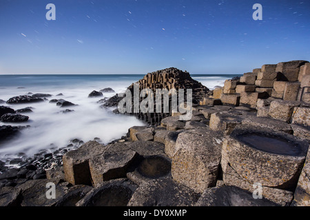 Starry night above the moonlit basalt columns at the Giant's Causeway UNESCO World Heritage site. - Stock Photo