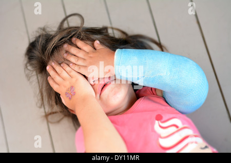 Abused little girl with a broken arm covering here face while crying. Concept photo of child abuse, domestic violent - Stock Photo