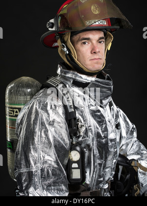Male firefighter in high temperature aviation fuel   firefighting uniform with breathing apparatus and axe - Stock Photo